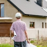 Image of a contractor with a hard hat and holding plans outside and walking towards a residental property