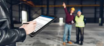 A person notating inspection on a tablet in the foreground. Two people in safety gear visually inspecting and pointing to something out of the image in the background.